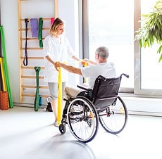 An elderly man in a wheelchair using a resistance band with the help of a physiotherapist.